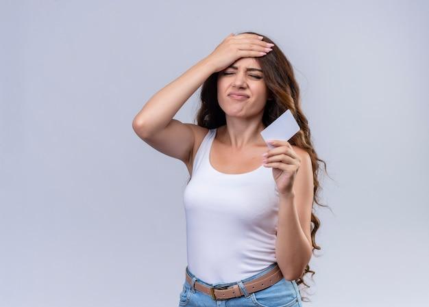 Подчеркнутая молодая красивая девушка держит кредитную карту и кладет руку на голову на изолированной белой стене с копией пространства