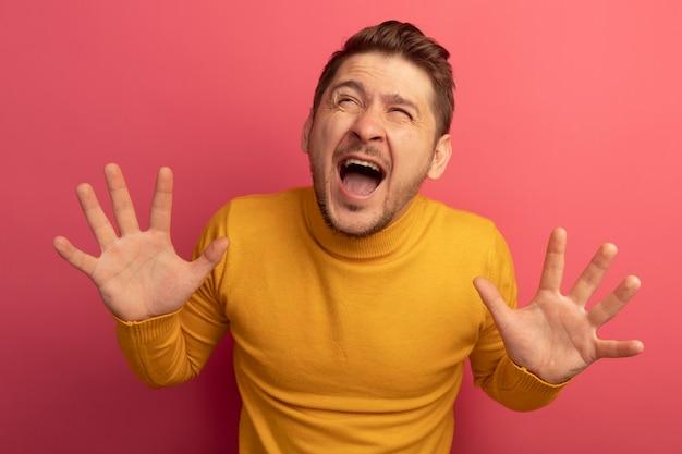Stressato giovane biondo bell'uomo che mostra le mani vuote alzando lo sguardo urlando