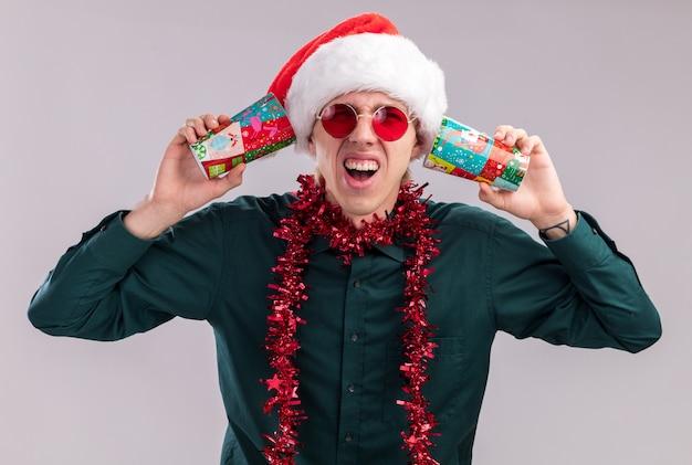 秘密を聞いて耳の横にプラスチック製のクリスマスカップを保持している首の周りに見掛け倒しの花輪とサンタの帽子と眼鏡を身に着けている若いブロンドの男を強調