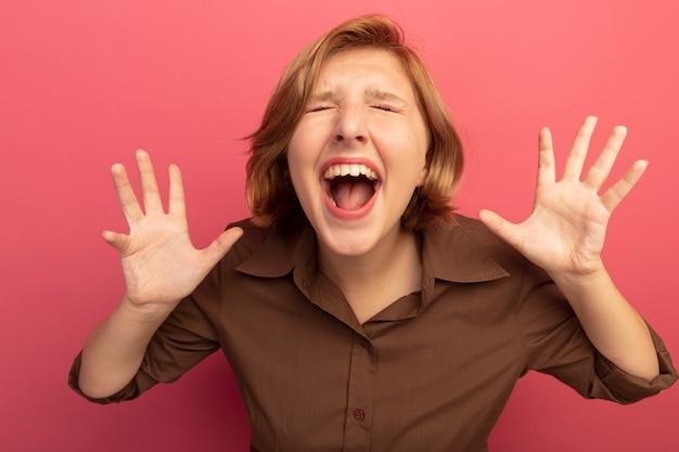 Giovane donna bionda stressata che urla con gli occhi chiusi che mostra le mani vuote