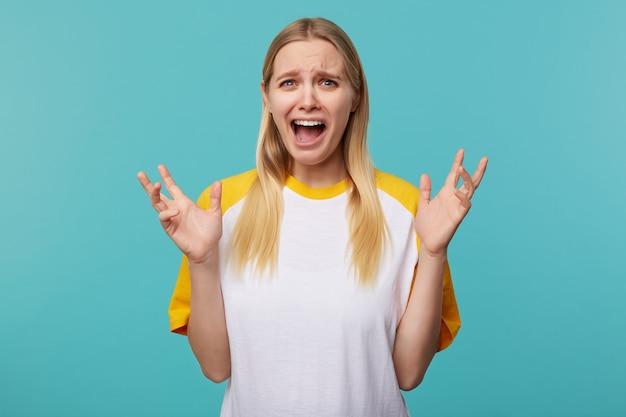 Sottolineato giovane donna bionda dagli occhi azzurri sollevando emotivamente le sue mani e gridando confusamente mentre guarda la telecamera, isolato su sfondo blu