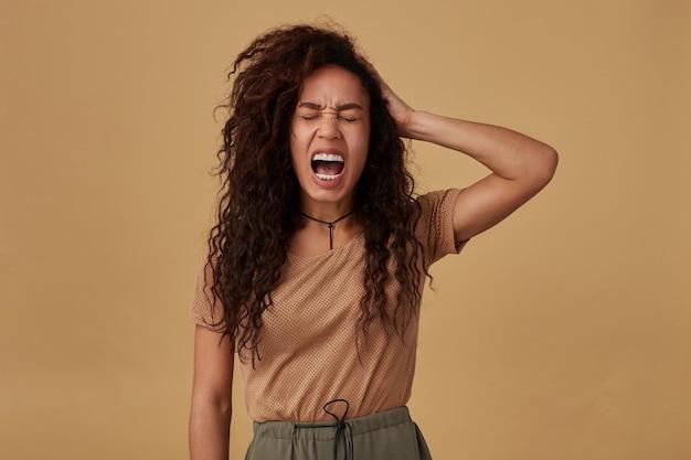 Sottolineato giovane signora dalla pelle scura riccia dai capelli castani che aggrotta le sopracciglia mentre urla e alza emotivamente la mano alla testa mentre posa sul beige
