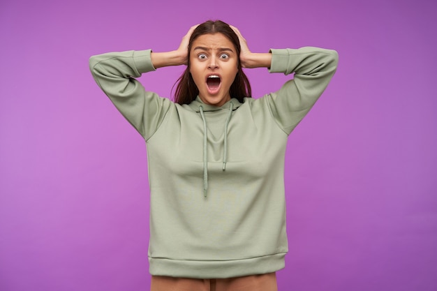 Stressed young brown haired woman dressed in mint hoodie clutching her head with raised hands while looking amazedly at front with wide mouth opened, posing over purple wall
