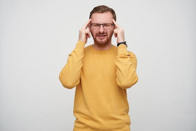 Sottolineato giovane brunetta ragazzo barbuto in occhiali aggrottando la fronte con gli occhi chiusi, mantenendo gli indici sulle tempie pur avendo forte mal di testa, isolato