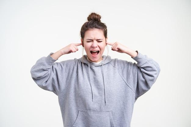 Sottolineato giovane donna bruna con acconciatura panino gridando con gli occhi chiusi e inserendo gli indici nelle orecchie, in piedi su sfondo bianco in abbigliamento sportivo