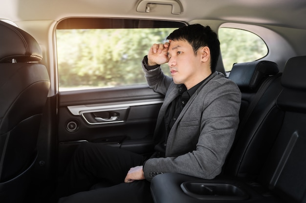 차 뒷좌석에 앉아 스트레스를 받는 젊은 사업가