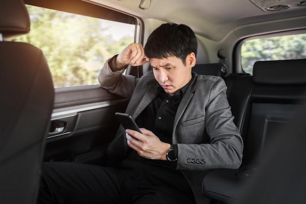 자동차 뒷좌석에 앉아 스마트폰을 사용하는 스트레스를 받는 젊은 사업가