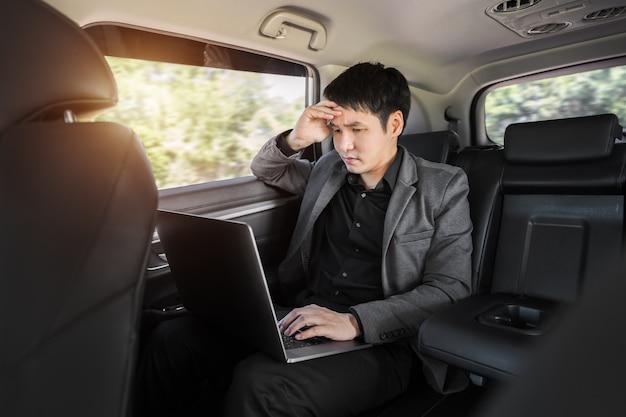 車の後部座席に座っている間ラップトップコンピューターを使用してストレスを抱えた若いビジネスマン
