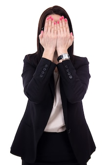Stressed young business woman crying and covering her face isolated on white background