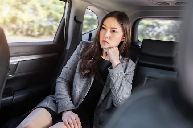 자동차 뒷좌석에 앉아 스트레스를 받는 젊은 비즈니스 우먼