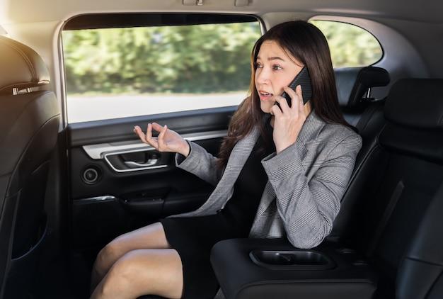 스트레스를 받은 젊은 비즈니스 여성은 차 뒷좌석에 앉아 휴대전화로 문제를 이야기하고 있다