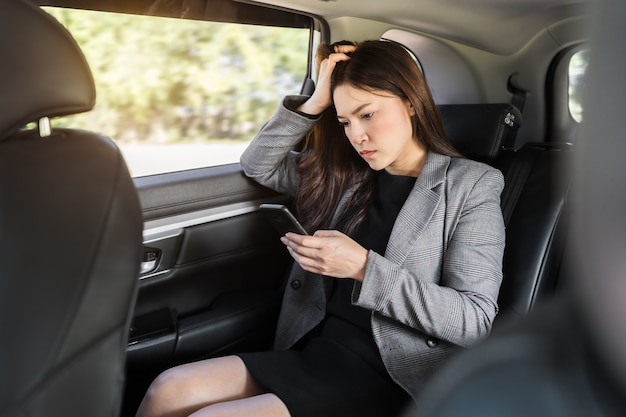 자동차 뒷좌석에 앉아 스마트폰을 사용하는 스트레스를 받는 젊은 비즈니스 여성