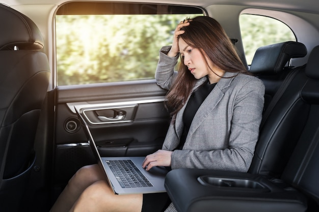 자동차 뒷좌석에 앉아 노트북 컴퓨터를 사용하는 스트레스를 받는 젊은 비즈니스 여성
