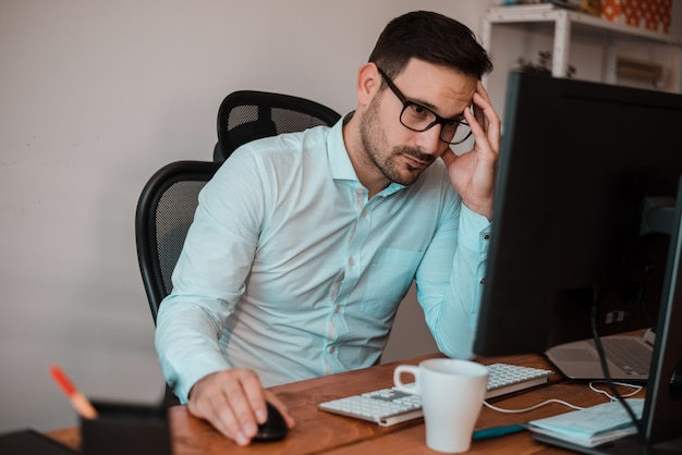 Stressed young businessman sitting in office working on computer holding head with hand.