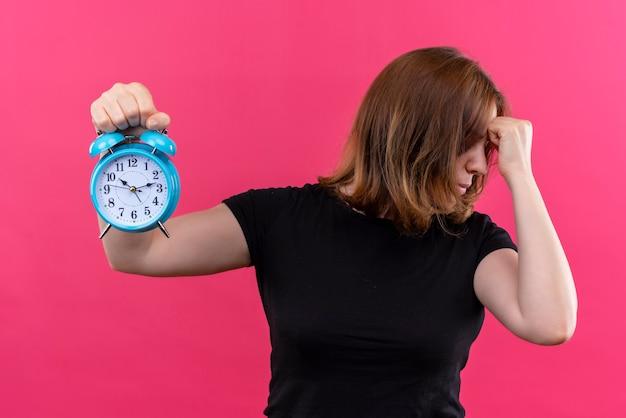 目覚まし時計を保持し、孤立したピンクの壁の額に拳を置くストレスの若いカジュアルな女性