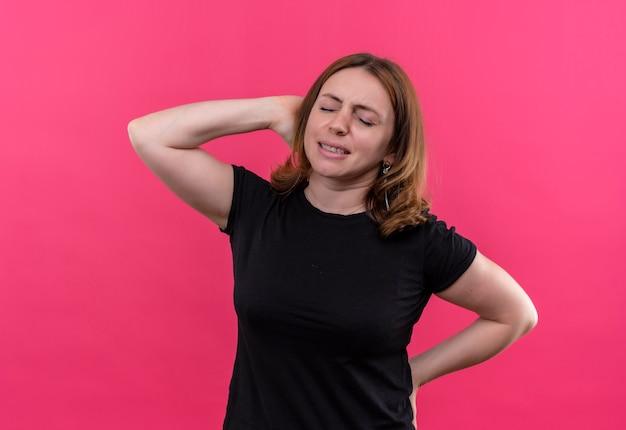 孤立したピンクの壁に頭の後ろと彼女の背中の後ろに手で強調された若いカジュアルな女性