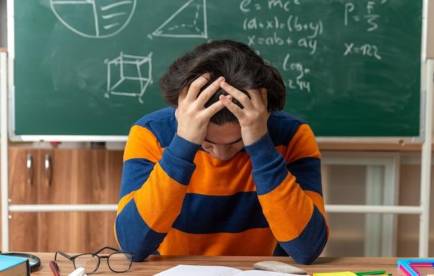 Giovane insegnante di geometria caucasica stressato con gli occhiali seduto alla scrivania con gli strumenti della scuola in classe tenendo le mani sulla testa Foto Gratuite