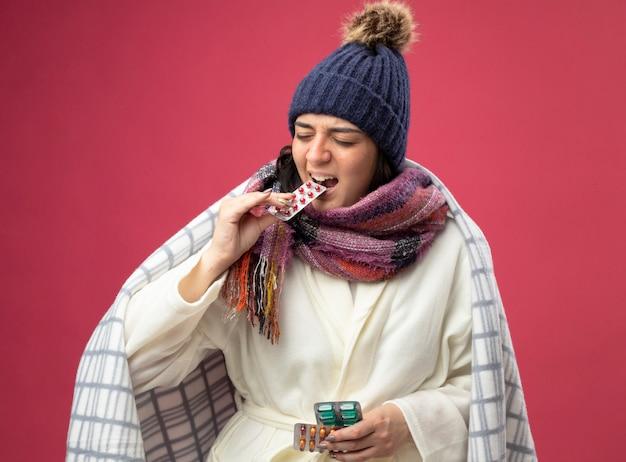 Подчеркнутая молодая кавказская больная девушка в зимней шапке и шарфе, завернутом в плед, держит пачки капсул, кусая одну из них с закрытыми глазами, изолированными на малиновом фоне