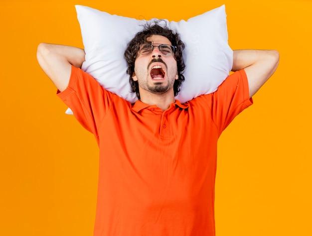 Sottolineato giovane uomo malato caucasico con gli occhiali tenendo il cuscino sotto la testa urlando con gli occhi chiusi isolati sulla parete arancione