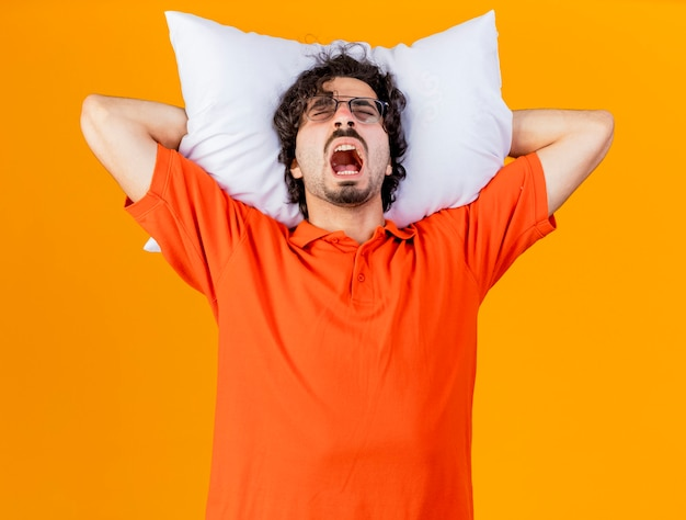 오렌지 벽에 고립 된 닫힌 눈으로 비명 머리 아래 베개를 들고 안경을 쓰고 젊은 백인 아픈 남자를 강조