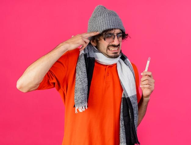 真っ赤な背景に分離された自殺ジェスチャーをしている温度計を保持しているカメラを見て眼鏡冬の帽子とスカーフを身に着けている若い白人の病気の男を強調