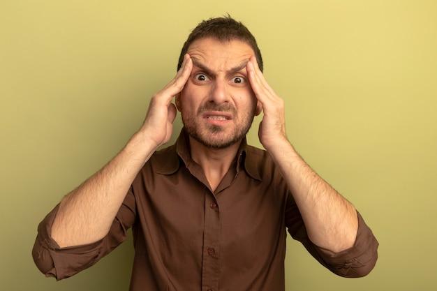 Sottolineato giovane uomo caucasico mettendo le mani sulla testa guardando la telecamera isolata su sfondo verde oliva