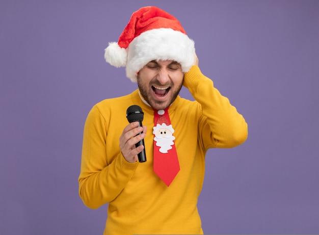 크리스마스 모자와 넥타이 복사 공간 보라색 배경에 고립 된 닫힌 된 눈으로 비명 머리에 손을 유지 마이크를 들고 입고 젊은 백인 남자를 강조 무료 사진
