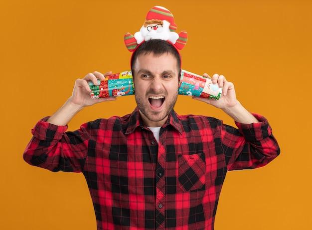 Sottolineato giovane uomo caucasico che indossa la fascia di babbo natale guardando il lato tenendo le tazze di plastica di natale accanto alle orecchie urlando isolato su sfondo arancione
