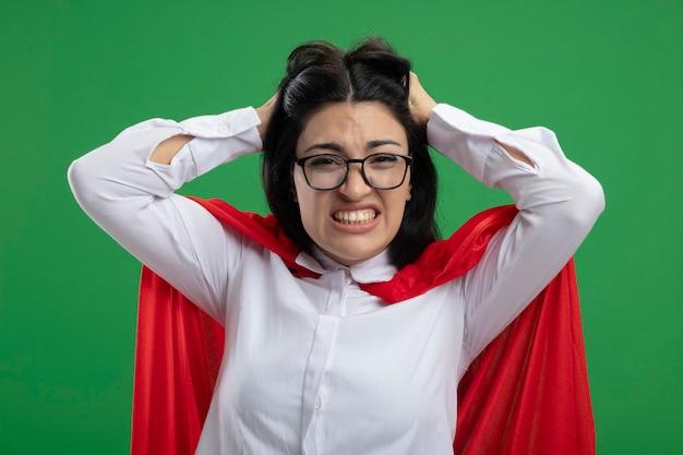 Ha sottolineato la giovane ragazza caucasica del supereroe con gli occhiali che tiene la sua testa e che mostra i denti che guarda l'obbiettivo isolato su priorità bassa verde