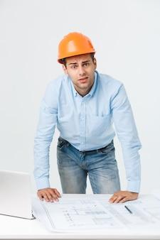 Giovane costruttore sollecitato che ha emicrania o emicrania che sembra esaurito e preoccupato isolato su fondo bianco con lo spazio della copia.