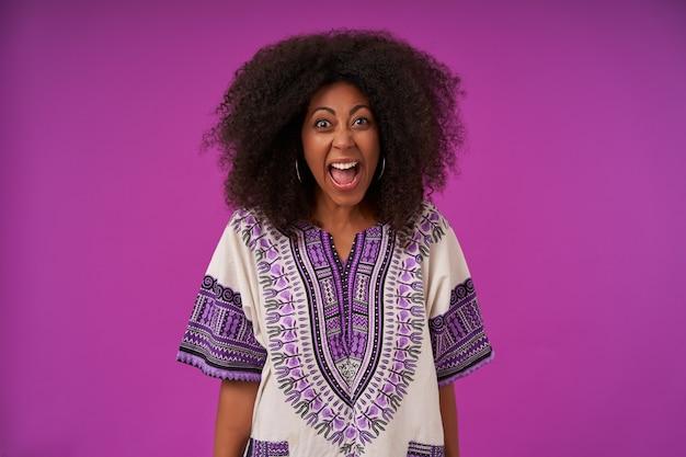 紫色に孤立したカジュアルな服を着て、怒って、広い口を開いて大声で叫んで、黒い肌の若い巻き毛の女性を強調
