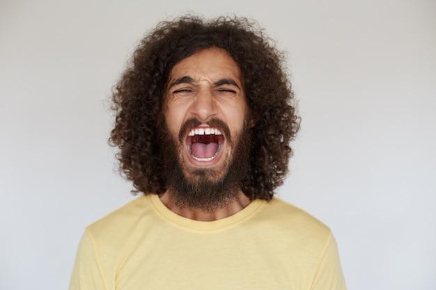 Подчеркнутый молодой темноволосый кудрявый мужчина с бородой громко кричит с широко открытым ртом и хмурится, держа руки опущенными во время позирования