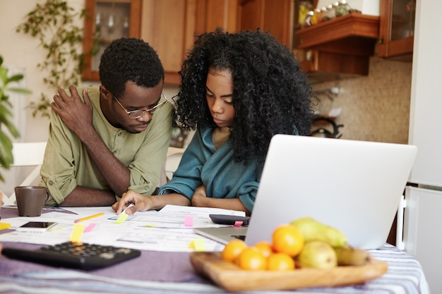 Подчеркнутая молодая темнокожая супружеская пара выглядит разочарованной, вместе подсчитывая внутренний бюджет, сидя за кухонным столом с кучей бумаг и портативным компьютером, пытаясь сэкономить