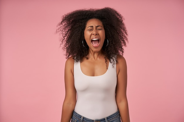 Sottolineato giovane donna dalla pelle scura con i capelli ricci in posa sul rosa con le mani verso il basso, aggrottando le sopracciglia il viso con gli occhi chiusi e urlando forte con la bocca larga aperta