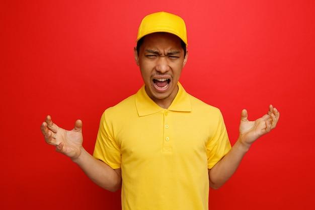모자와 제복을 입은 젊은 배달 남자가 비명을 지르는 빈 손을 보여주는 스트레스