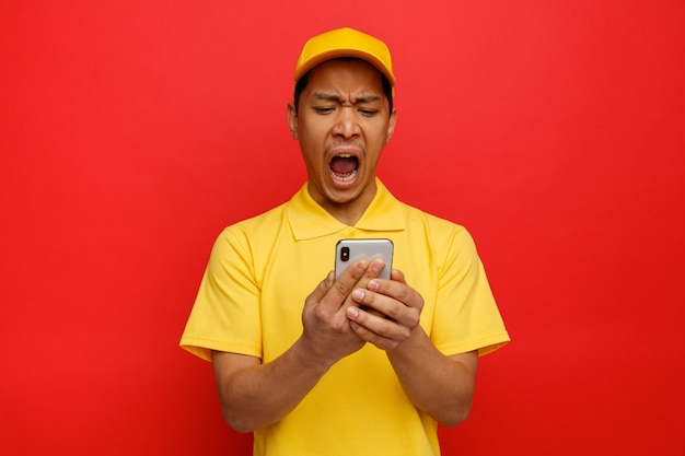 Stressed young delivery man wearing cap and uniform holding and looking at mobile phone screaming