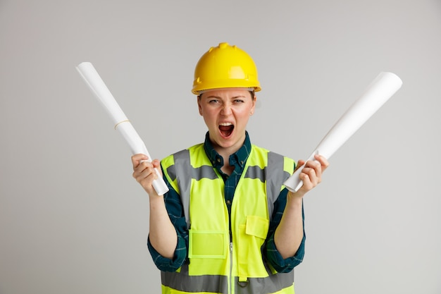 비명을 지르는 서류를 들고 안전 헬멧과 안전 조끼를 입고 젊은 여성 건설 노동자를 강조