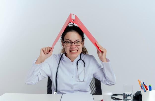 Sottolineato giovane medico femminile che indossa veste medica e stetoscopio e occhiali seduto alla scrivania con strumenti medici alla ricerca di cartelle di contenimento sulla testa isolata