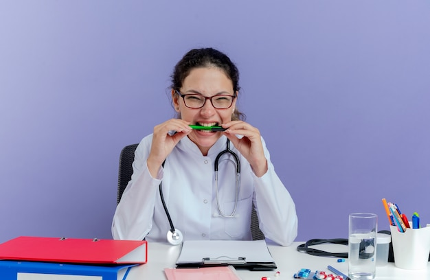 Sottolineato giovane medico femminile che indossa abito medico e stetoscopio seduto alla scrivania con strumenti medici alla ricerca di penna mordace isolata