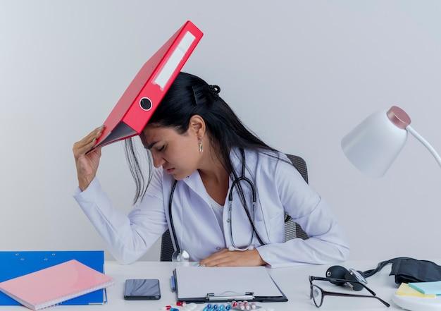 Sottolineato giovane medico femminile che indossa veste medica e stetoscopio seduto alla scrivania con strumenti medici mettendo la mano sulla scrivania toccando la testa con la cartella con gli occhi chiusi isolati