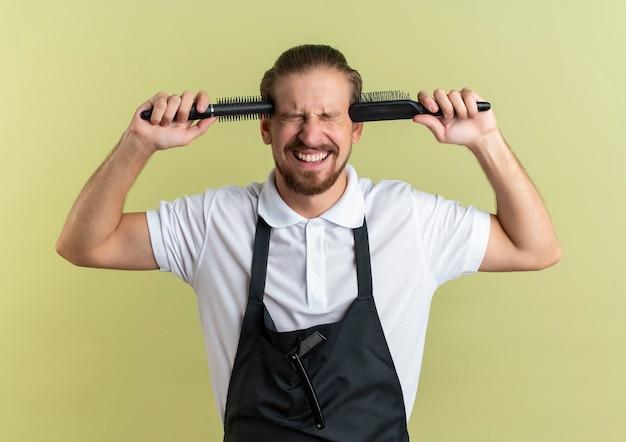 Sottolineato giovane barbiere bello che mette pettini sulle tempie con gli occhi chiusi isolati sulla parete verde oliva