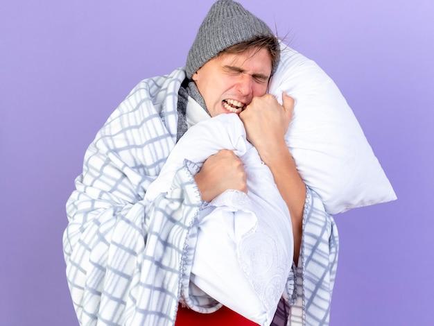 冬の帽子とスカーフを身に着けている若いハンサムな金髪の病気の男が紫色の背景で隔離の目を閉じて叫んで格子縞の保持枕に包まれて強調