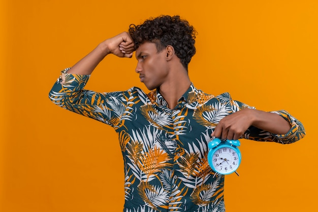 Stressed young handsome dark-skinned man with curly hair in leaves printed shirt holding blue alarm clock and showing time on an orange background