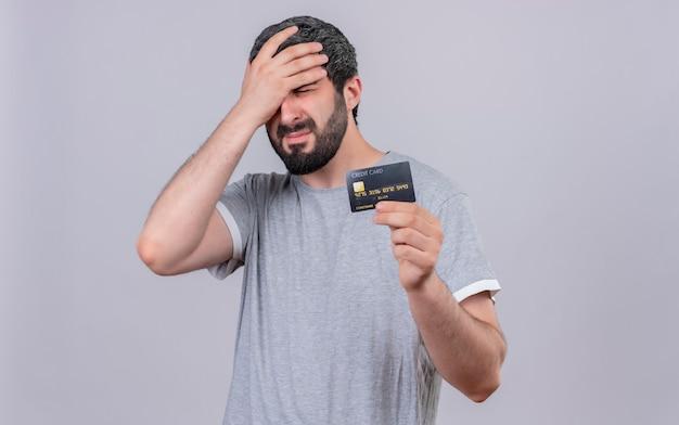 Sottolineato giovane uomo bello che tiene la carta di credito e che mette la mano sulla testa con gli occhi chiusi isolati sulla parete bianca