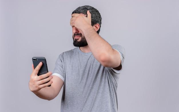 Sottolineato giovane uomo bello che tiene il telefono cellulare e mettendo la mano sulla fronte con gli occhi chiusi isolati sul muro bianco