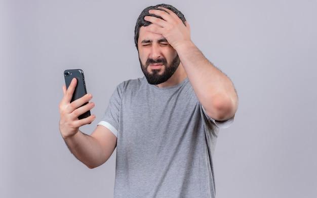 Sottolineato giovane uomo bello che tiene il telefono cellulare mettendo la mano sulla testa con gli occhi chiusi isolati sulla parete bianca