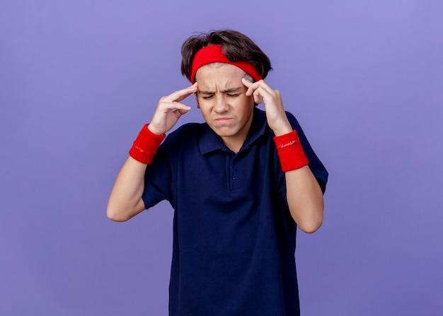 コピースペースのある紫色の壁に隔離された目を閉じて頭に触れる歯科用ブレース付きのヘッドバンドとリストバンドを身に着けている若いハンサムなスポーティな少年を強調