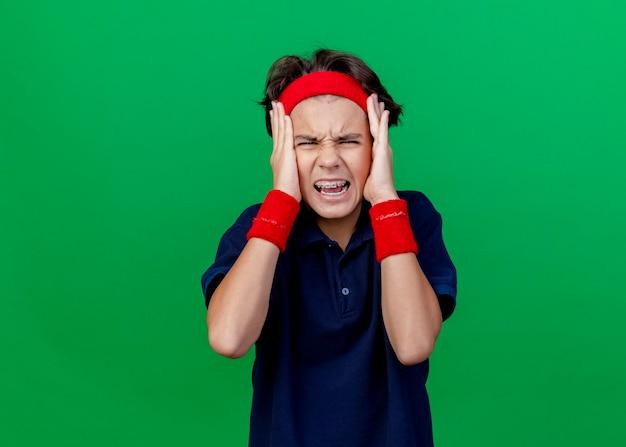 Sottolineato giovane bel ragazzo sportivo che indossa la fascia e braccialetti con bretelle dentali mantenendo le mani sulla testa guardando la telecamera isolata su sfondo verde con spazio di copia