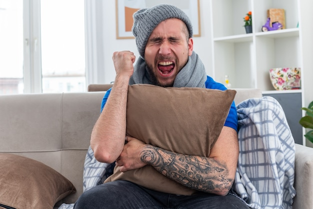 Stressed young ill man wearing scarf and winter hat sitting on sofa in living room hugging pillow clenching fist screaming with closed eyes