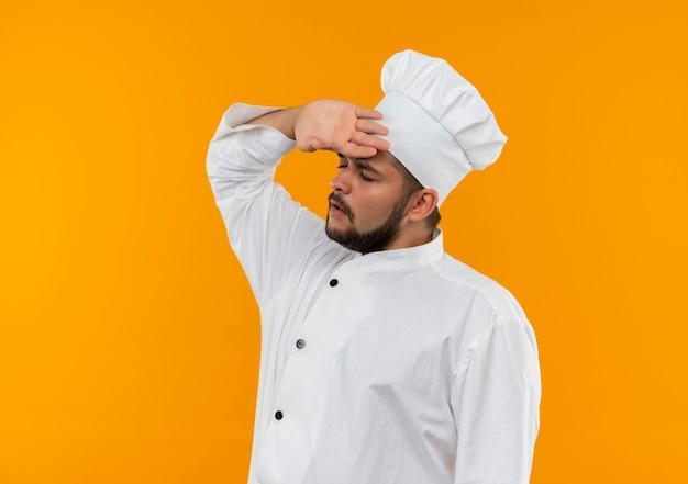 Sottolineato giovane cuoco maschio in uniforme del cuoco unico che mette la mano sulla fronte con gli occhi chiusi isolati su spazio arancione